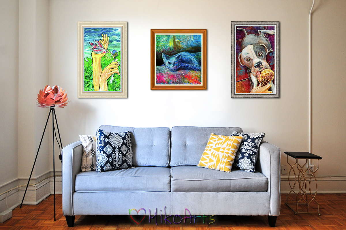 A living room with three of my museum quality framed prints hanging over a blue couch. The artworks are a Feeding Angels, a hummingbird painting. Blue Cat Not Say, a blue cat painting, and Odin Gets a Treat!, a painting of a little Pit Bull Puppy eating an ice cream cone.